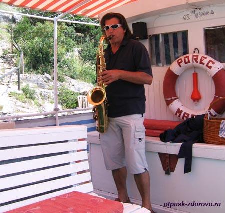 Лимский канал (фьорд), полуостров Истрия, Хорватия, капитан корабля играет на саксофоне
