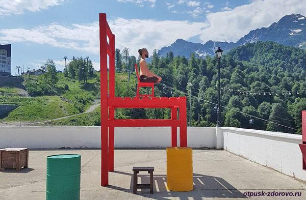 Медитация на гигантских стульях с видом на канатную дорогу в Олимпийской деревне